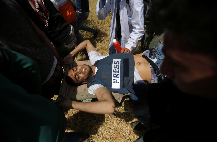 Mortally wounded Palestinian journalist Yasser Murtaja, 31, is evacuated during clashes with Israeli troops at the Israel-Gaza border, in the southern Gaza Strip April 6, 2018. (photo credit: IBRAHEEM ABU MUSTAFA / REUTERS)