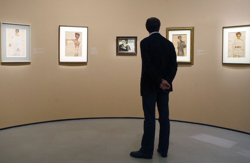 A man looks at self-portraits by Egon Schiele at the Belvedere museum in Vienna  (photo credit: REUTERS/HERWIG PRAMMER)