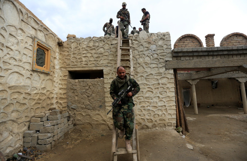 Afghan Special Forces walk down from a roof of a house which was used by suspected Islamic State militants at the site of a ''mother of all bombs'', that struck the Achin district of Afghanistan April 23, 2017. (photo credit: REUTERS/PARWIZ)