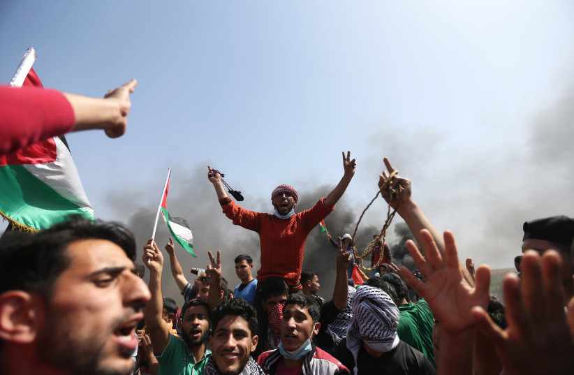 Palestinian demonstrators during a protest on the Israel-Gaza border east of the Jabalia refugee camp in the northern Gaza Strip on April 6, 2018. (photo credit: MOHAMMED ABED / AFP)