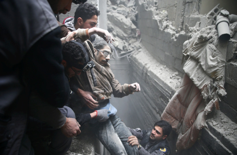 Civil defense help a man from a shelter in the besieged town of Douma in eastern Ghouta in Damascus, Syria, February 22, 2018. (photo credit: REUTERS/BASSAM KHABIEH)