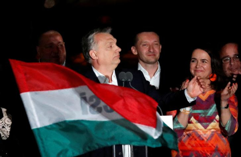 Hungarian Prime Minister Viktor Orban addresses supporters after the announcement of the partial results of parliamentary election in Budapest, Hungary, April 8, 2018 (photo credit: BERNADETT SZABO / REUTERS)
