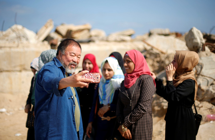 Chinese artist Ai Weiwei takes a selfie with Palestinian girls as he works on a documentary film on refugees, at the Seaport of Gaza City May 12, 2016 (photo credit: MOHAMMED SALEM/REUTERS)