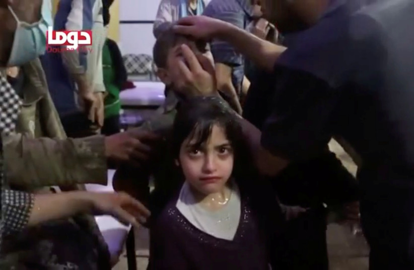 A girl looks on following alleged chemical weapons attack, in what is said to be Douma, Syria in this still image from video obtained by Reuters on April 8, 2018 (photo credit: WHITE HELMETS/REUTERS TV VIA REUTERS)