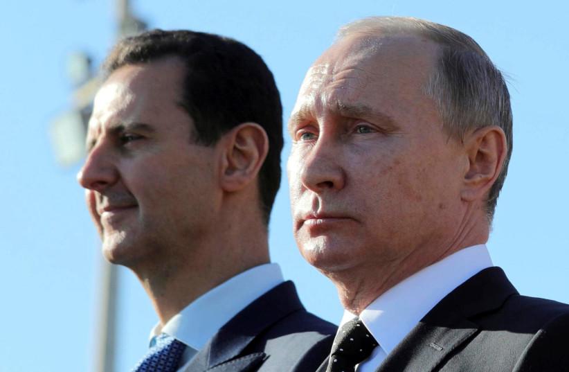 Russian President Vladimir Putin (R) and Syrian President Bashar al-Assad visit the Hmeymim air base in Latakia Province, Syria December 11, 2017 (photo credit: SPUTNIK/MIKHAIL KLIMENTYEV/ VIA REUTERS)
