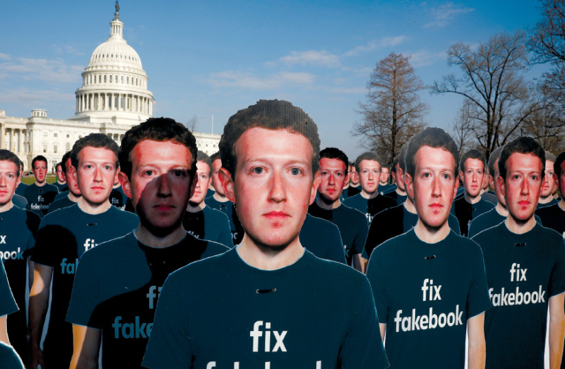 DOZENS OF cardboard cutouts of Facebook CEO Mark Zuckerberg are seen during a protest outside the US Capitol in Washington, April 2018 (photo credit: AARON P. BERNSTEIN/ REUTERS)