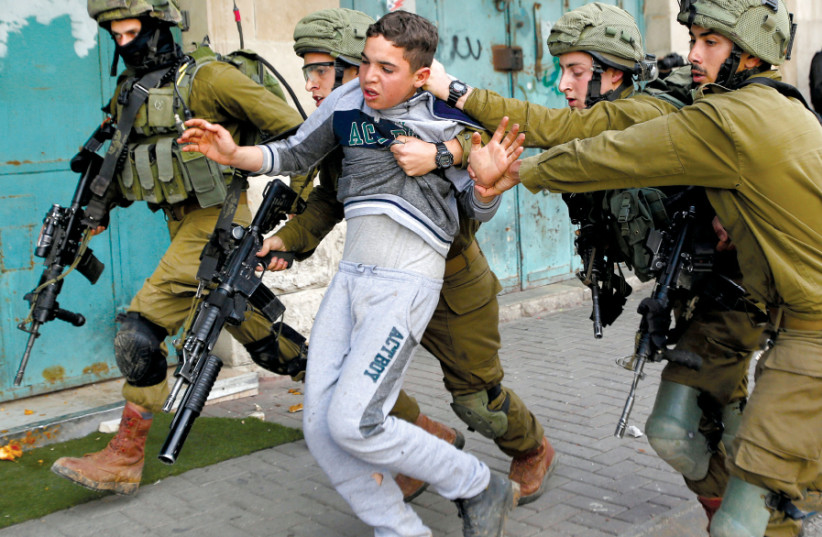 IDF SOLDIERS detain a Palestinian during clashes at a protest in Hebron in February (photo credit: REUTERS/MUSSA QAWASMA)
