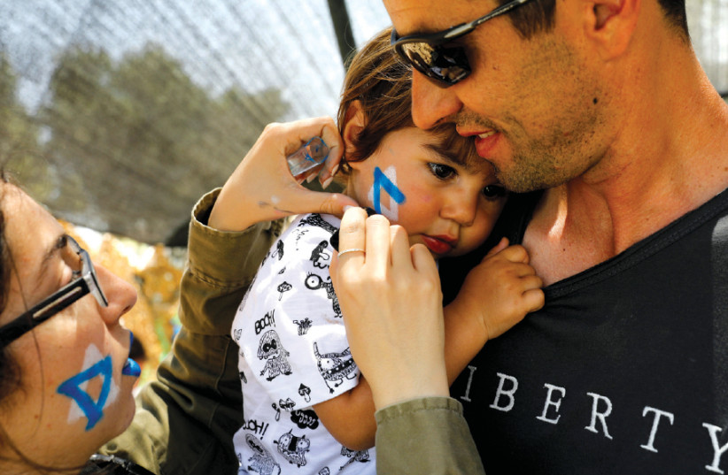 A SOLDIER paints a Star of David on a child's cheek during a display of IDF equipment and capabilities, as part of the celebrations for Independence Day in Sderot, 2017 (photo credit: AMIR COHEN/REUTERS)