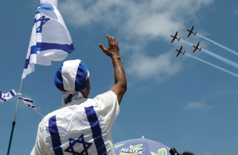 PEOPLE WATCH the Israel Air Force Aerobatic team fly over the Mediterranean Sea during Independence Day celebrations in Tel Aviv, 2017 (photo credit: AMMAR AWAD/REUTERS)