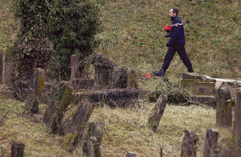 A French Gendarme walks by some of 250 desecrated tombstones at the Sarre-Union Jewish cemetery, near Strasbourg, in this file photo (photo credit: VINCENT KESSLER/ REUTERS)