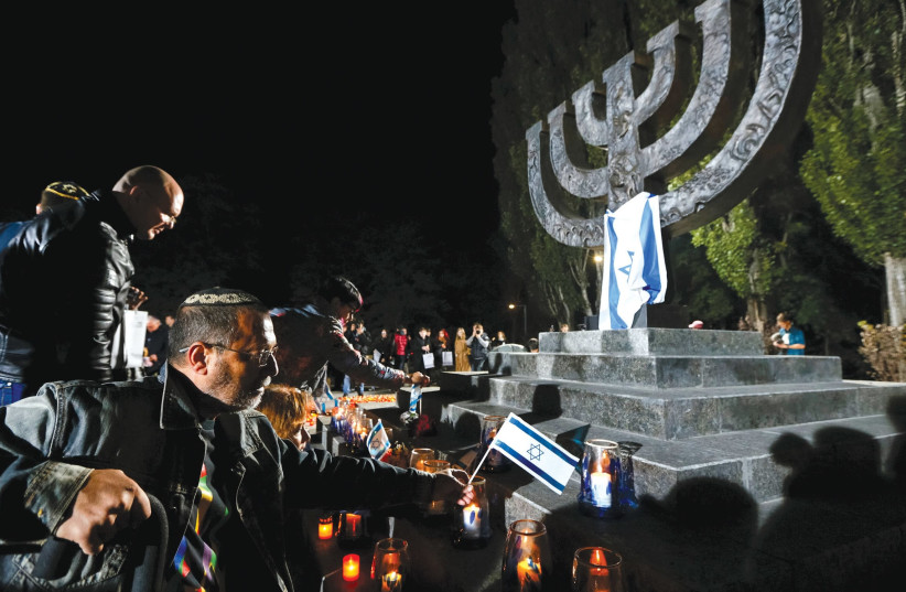 People place candles in 2016 and fly Israeli flags during a ceremony commemorating the victims of Babi Yar, one of the biggest single massacres of Jews during the Holocaust, next to Kiev (photo credit: REUTERS)