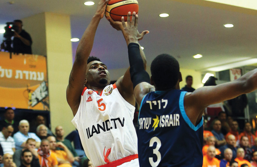 Maccabi Rishon Lezion guard Keith Langford (5) shoots over Hapoel Eilat's Jordan Loyd during a 73-66 win for Rishon over Eilat in BSL action. (photo credit: UDI ZITIAT)