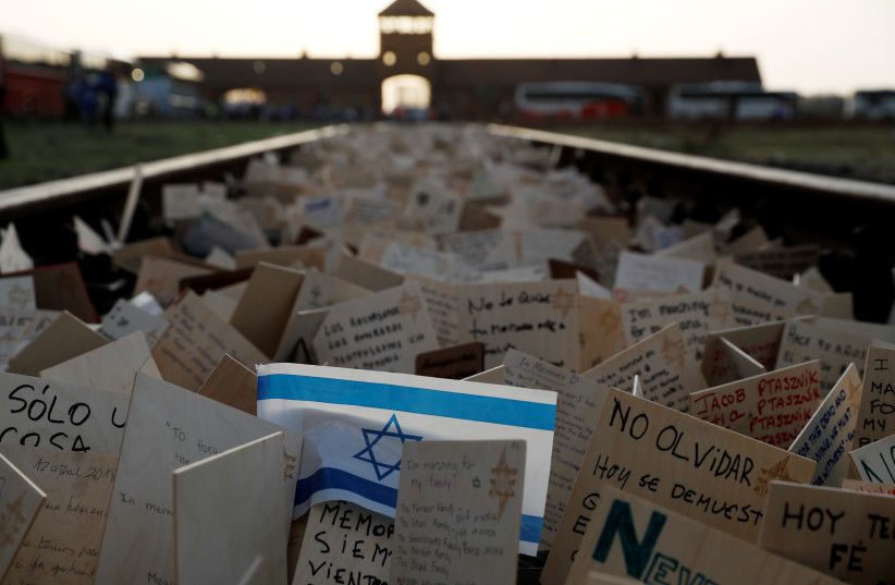 "Cards are placed between railway tracks in the former Nazi death camp Auschwitz as people take part in the annual ""March of the Living"" to commemorate the Holocaust, in Oswiecim, Poland, April 12, 2018.  (photo credit: REUTERS/KACPER PEMPEL)"