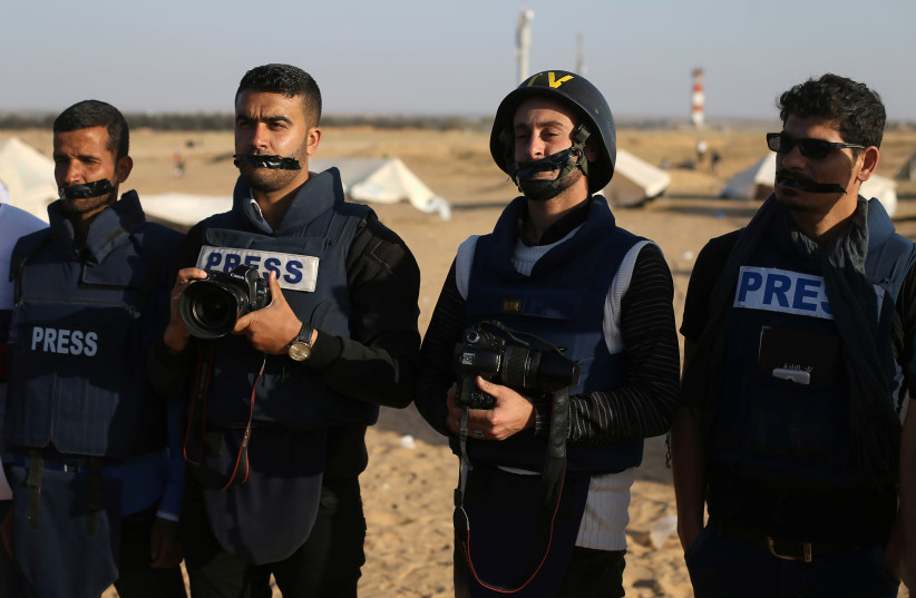Journalists take part in a protest against the killing of Palestinian journalist Yasser Murtaja, at the Israel-Gaza border, in the southern Gaza Strip April 8, 2018. (photo credit: REUTERS/IBRAHEEM ABU MUSTAFA)