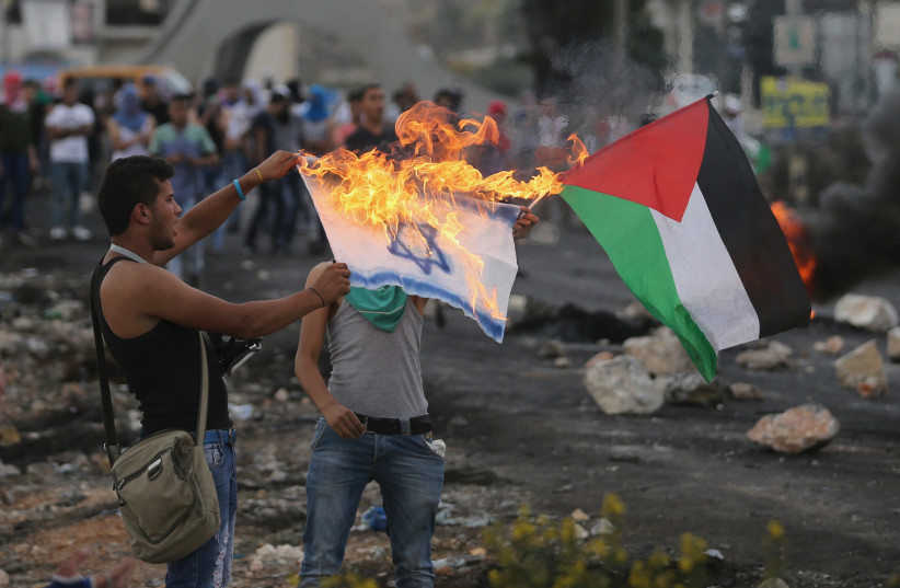 A Palestinian protester burns a replica Israeli flag as another holds a Palestinian flag during clashes with the Israeli troops near the Jewish settlement of Bet El, near the West Bank city of Ramallah October 18, 2015. (photo credit: MOHAMAD TOROKMAN/REUTERS)