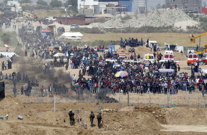 A picture taken on April 13, 2018 from the southern Israeli kibbutz of Nahal Oz across the border with the Gaza Strip shows Israeli soldiers keeping position and Palestinian protestors gathering along the border fence with Israel. Several thousand Gazans gathered for a third consecutive Friday of ma (photo credit: JACK GUEZ / AFP)