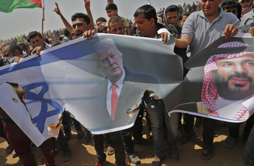 Palestinians prepare to set fire on an Israeli flag and portraits of US President Donald Trump and Saudi Crown Prince Mohammed bin Salman during a protest at the border fence with Israel, east of Khan Yunis in the southern Gaza city, on April 13, 2018 (photo credit: THOMAS COEX / AFP)