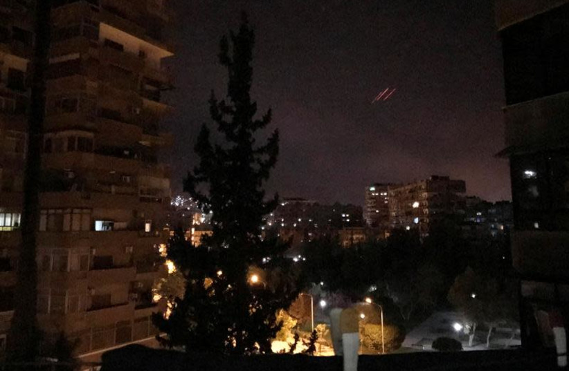 Anti-aircraft fire is seen over Damascus,Syria early April 14, 2018.  (photo credit: REUTERS/FERAS MAKDESI)