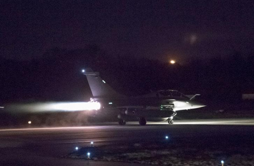 A plane preparing to take off as part of the joint airstrike operation by the British, French and US militaries in Syria, is seen in this picture obtained on April 14, 2018 via social media (photo credit: COURTESY FRENCH MILITARY/TWITTER/VIA REUTERS)