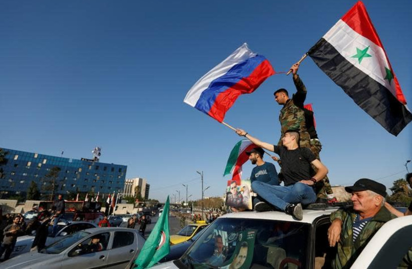 Syrians wave Russian and Syrian flags during a protest against US-led air strikes in Damascus,Syria April 14,2018 (photo credit: OMAR SANADIKI/REUTERS)