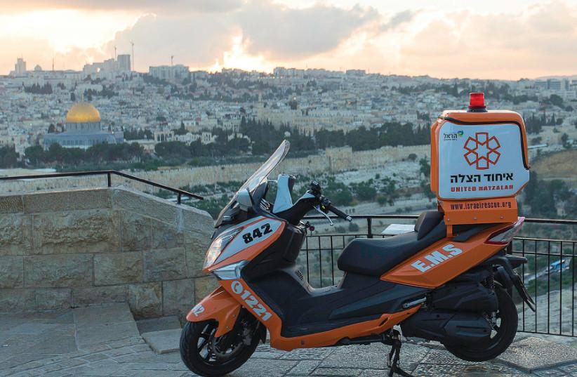 A UNITED HATZALAH ambucycle is seen with Jerusalem in the background (photo credit: SHIRA HERSHKOPF/UNITED HATZALAH)