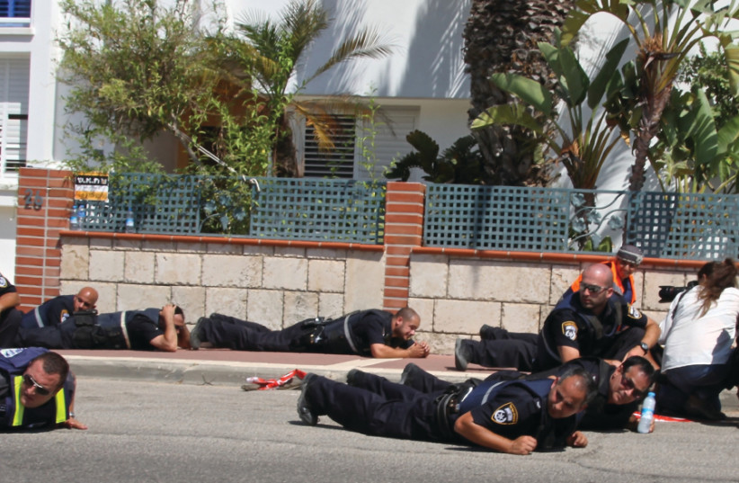Police officers duck for cover in Sderot as a siren wails in the background during Operation Protective Edge (photo credit: TOVAH LAZAROFF)