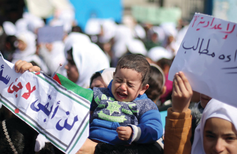 A PALESTINIAN BOY cries as students of United Nations-run schools take part in a protest against a US decision to cut aid, in Khan Yunis in the southern Gaza Strip, February 2017 (photo credit: REUTERS)