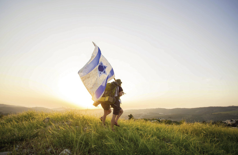 Two hikers carry an Israeli flag near Castel as part of the Masa 70 trek  (photo credit: TOMER BEN-AVI)