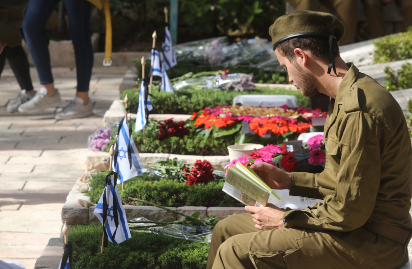 An Israeli soldier sits by a grave on Mount Herzl during Remembrance Day on April 18th, 2018. (photo credit: MARC ISRAEL SELLEM/THE JERUSALEM POST)
