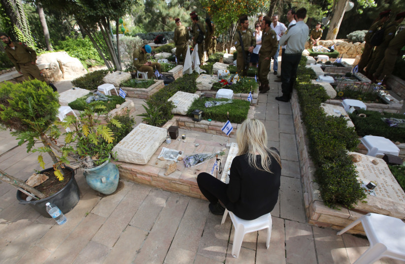 An Israeli sits near a grave during Remembrance Day on April 18th, 2018. (photo credit: MARC ISRAEL SELLEM/THE JERUSALEM POST)