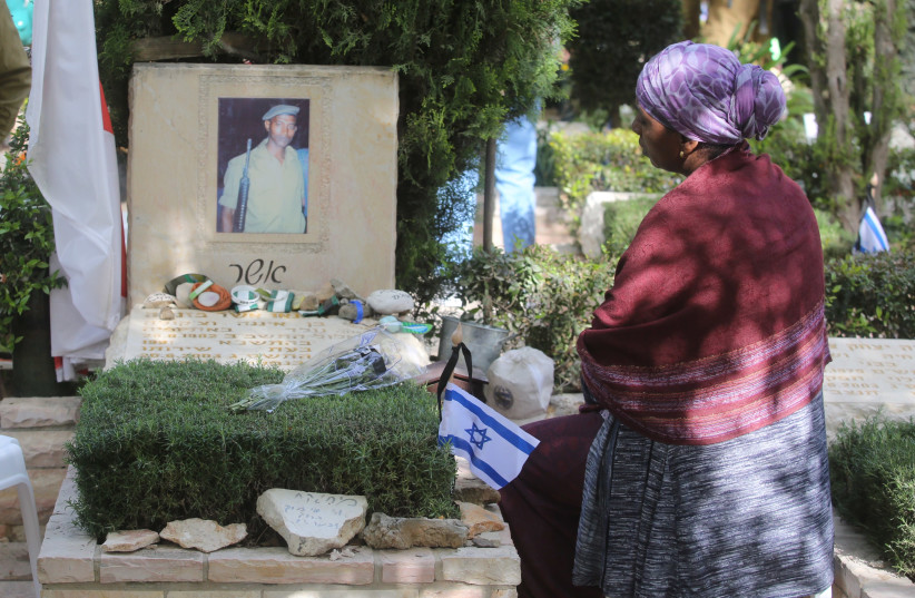 An Israeli visits the grave of a fallen soldier on Mount Herzl during Remembrance Day on April 18th, 2018. (photo credit: MARC ISRAEL SELLEM/THE JERUSALEM POST)