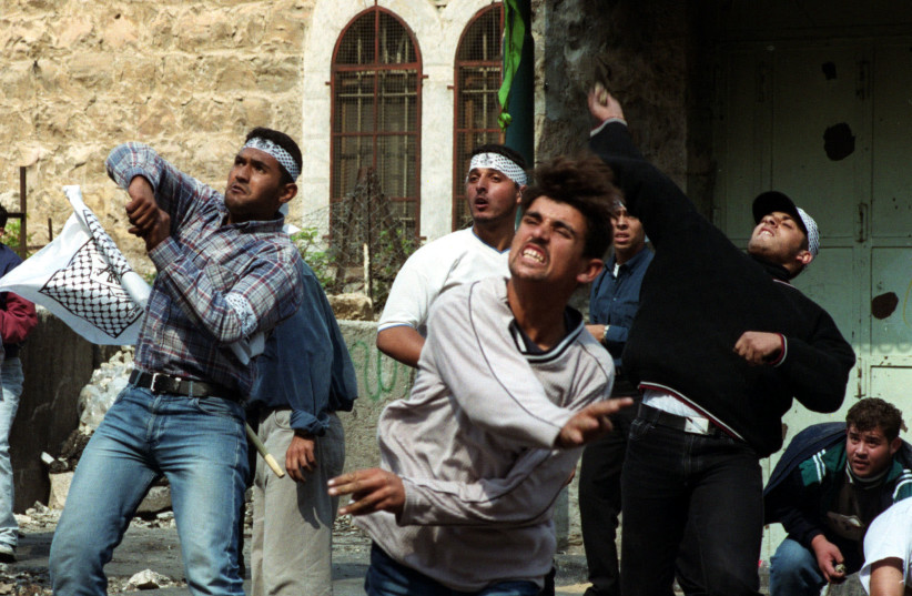 Palestinians hurl rocks at Israeli security forces during clashes in the West Bank town of Hebron October 16, 2000. (photo credit: REUTERS)