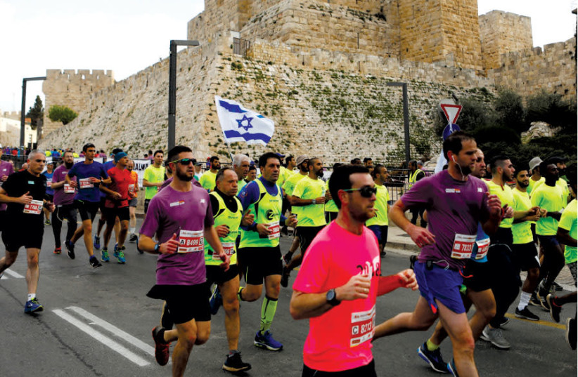 ATHLETES RUN outside the Old City during the eighth International Jerusalem Marathon, April 2018 (photo credit: RONEN ZVULUN / REUTERS)