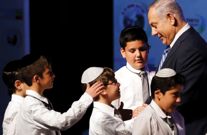 PRIME MINISTER Benjamin Netanyahu shakes hands with children during a regional development conference in Dimona, March 2018 (photo credit: RONEN ZVULUN / REUTERS)