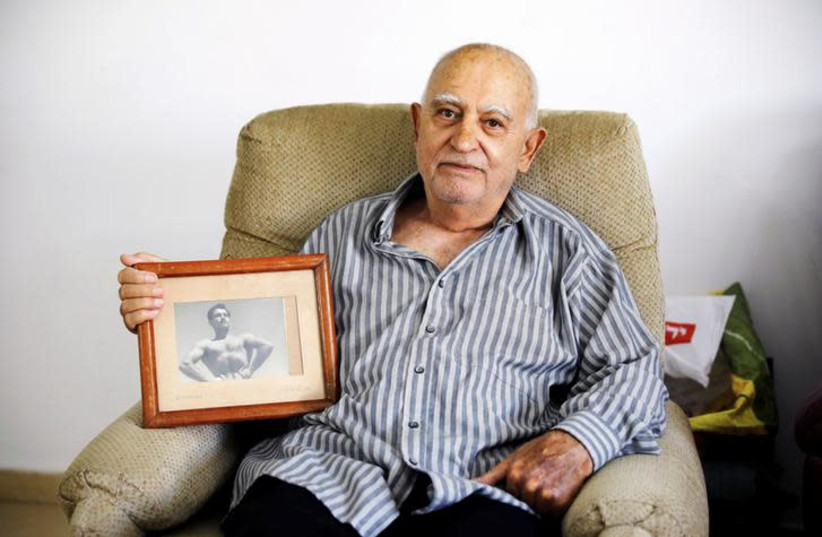 Aharon Ben Hur, 84, who immigrated from Iraq to Israel in 1951, holds an old photo of himself in his house in Rehovot, Israel, April 16, 2018. Picture taken April 16, 2018. (photo credit: AMIR COHEN/REUTERS)