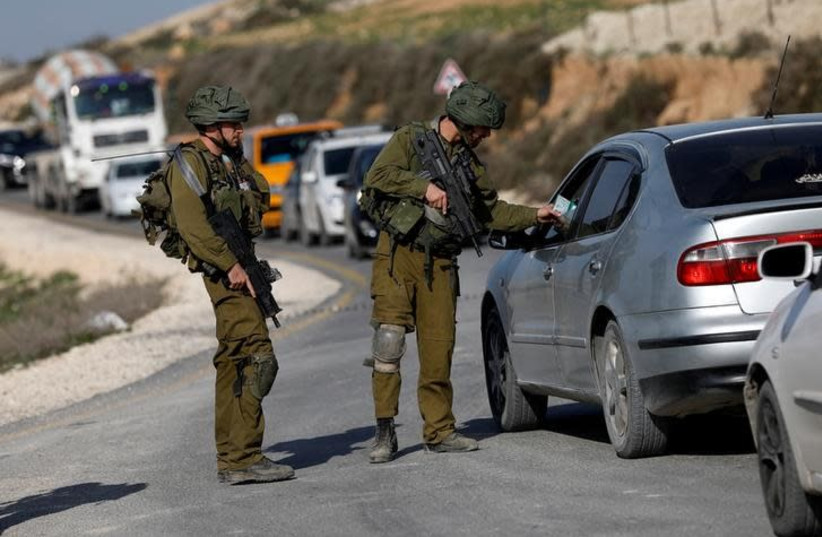 An Israeli solider looks at ID of a Palestinian man at a checkpoint near the West Bank city of Nablus January 10, 2018 (photo credit: REUTERS/MOHAMAD TOROKMAN)