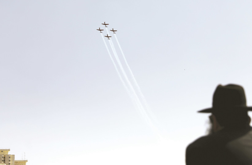 An ultra-Orthodox man watches planes fly overhead. (photo credit: REUTERS)
