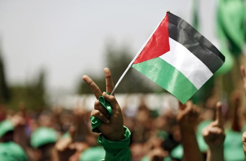 A student supporting Hamas holds a Palestinian flag in a rally during an election campaign for the student council at the Birzeit University in the West Bank city of Ramallah April 26, 2016 (photo credit: MOHAMAD TOROKMAN/REUTERS)