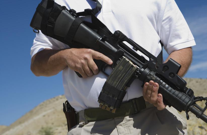 Man holding a machine gun (illustrative) (photo credit: INGIMAGE)