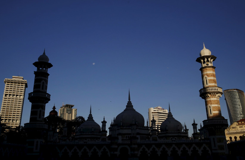 A mosque is silhouetted against city buildings in Kuala Lumpur, Malaysia, January 27, 2016. (photo credit: OLIVIA HARRIS/ REUTERS)