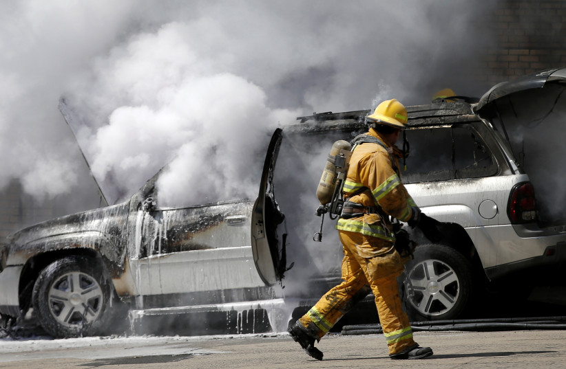 A firefighter approaches a burning car in New York City (photo credit: MIKE SEGAR / REUTERS)