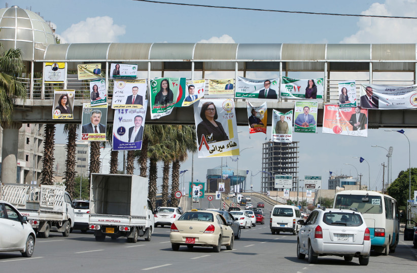 Vehicles drive under campaign posters ahead of the parliamentary election, in Erbil, Iraq (photo credit: AZAD LASHKARI / REUTERS)