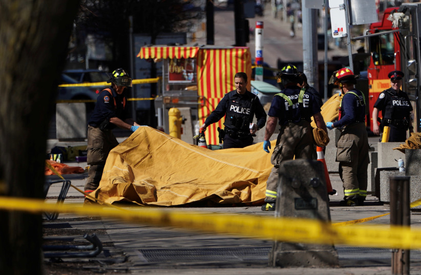 Firemen cover a victim of an incident where a van struck multiple people at a major intersection in Toronto's northern suburbs, in Toronto, Ontario, Canada, April 23, 2018 (photo credit: CARLO ALLEGRI/REUTERS)