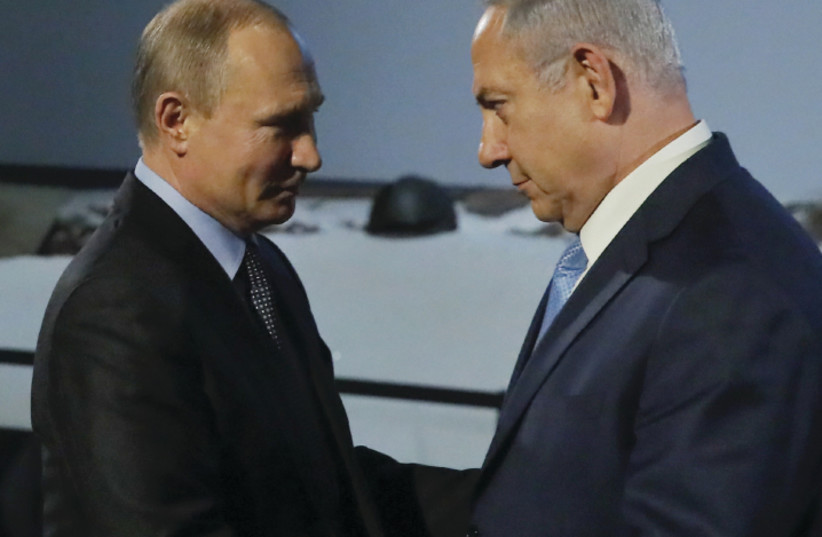 Russian President Vladimir Putin and Israeli Prime Minister Benjamin Netanyahu shake hands as they attend an event marking International Holocaust Remembrance Day and the 75th anniversary of the breakthrough of the Nazi siege of Leningrad in World War II, at the Jewish Museum and Tolerance Center in (photo credit: REUTERS/MAXIM SHEMETOV)