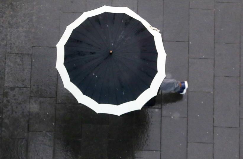 A person walks with an umbrella during a rain storm in Jerusalem, April 25, 2018 (photo credit: MARC ISRAEL SELLEM/THE JERUSALEM POST)
