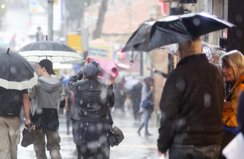 People seek shelter during a rain storm in Jerusalem, April 25, 2018 (photo credit: MARC ISRAEL SELLEM/THE JERUSALEM POST)