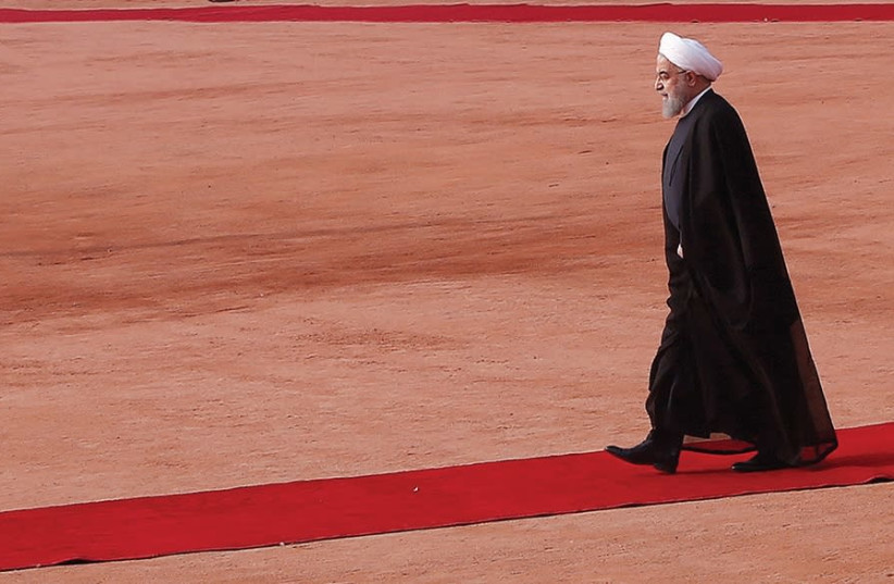 Iranian President Hassan Rouhani walks on a red carpet in Tehran (photo credit: REUTERS)