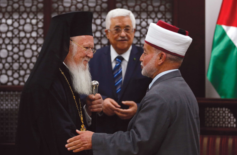 Grand Mufti of Jerusalem Muhammad Ahmad Hussein (R) shakes hands with Ecumenical Orthodox Patriarch Bartholomew I of Constantinople during a meeting with Palestinian President Mahmoud Abbas (C) in the West Bank city of Ramallah in 2014 (photo credit: REUTERS)