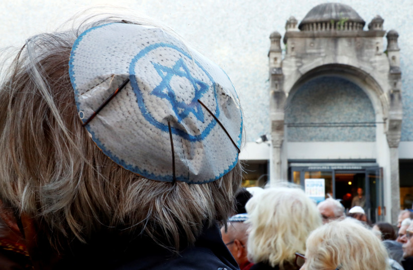People wear kippas as they attend a demonstration in front of a Jewish synagogue, to denounce an anti-Semitic attack on a young man wearing a kippa in the capital earlier this month, in Berlin, Germany, April 25, 2018. (photo credit: FABRIZIO BENSCH / REUTERS)