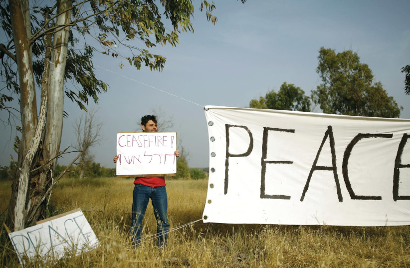 A PEACE activist holds up a sign near Gaza. (photo credit: REUTERS)